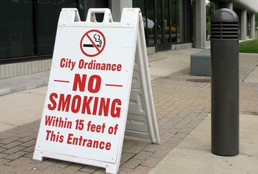 A sign reading City Ordinance No Smoking Within 15 Feet of This Entrance