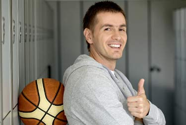 A man leaning against a basketball against a wall giving a thumbs up