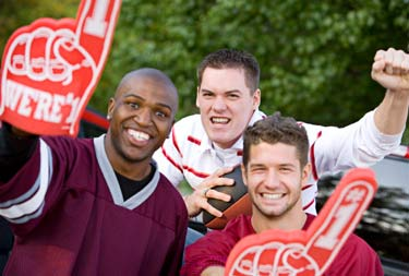 Three young men tailgating and cheering